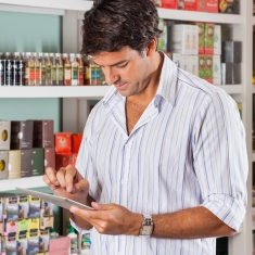 Mid adult man using digital tablet in grocery store